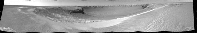 "Opportunity edgedclose to the top of the ""Duck Bay"" alcove along the rim of Victoria Crater during the rover's 952nd Martian day, or sol (overnight September 27 to 28), and gained this vista of the crater. The rover's navigation camera took several exposures combined into this mosaic view of the crater's interior. The far side of the crater is about 800 meters (one-half mile) away. The rim of the crater is composed of alternating promontories, rocky points towering approximately 70 meters (230 feet) above the crater floor, and recessed alcoves, such as Duck Bay. (Photo by NASA/JPL-Caltech/The Atlantic)"