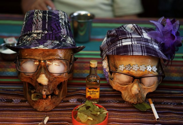 """Skulls of Paulino and Juanita are seen on a table a day before the """"Dia de los natitas"""" (Day of the Skull) celebrations at the General Cemetery of La Paz November 7, 2014. Bolivians, who keep close relatives' skulls at home as a macabre talisman, flock to the cemetery chapel once a year to have the craniums blessed and to bring themselves good luck in the future. Picture taken on November 7. (Photo by David Mercado/Reuters)"""
