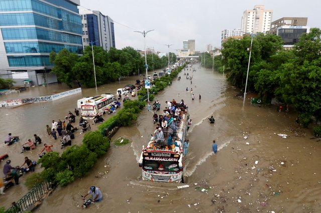 People sit atop a bus roof while others wade through the flooded road during monsoon rain, as the outbreak of the coronavirus disease (COVID-19) continues, in Karachi, Pakistan on August 27, 2020. (Photo by Akhtar Soomro/Reuters)