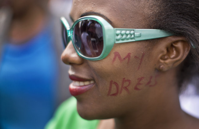 "A Kenyan woman with part of the slogan ""My dress, my choice"" written on her cheeks, protests with others for the right to wear whichever clothes they want, at a demonstration in downtown Nairobi, Kenya Monday, November 17, 2014. (Photo by Ben Curtis/AP Photo)"