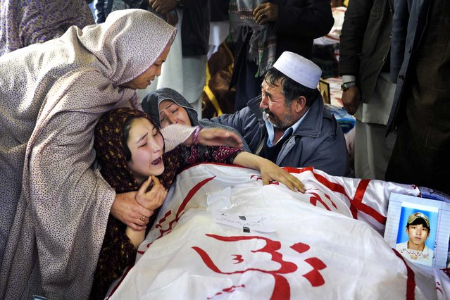 A woman is comforted by relatives while grieving over the body of her brother Mohammed Ali, who was killed in a weekend bombing targeting minority Shiite Muslims in Quetta, Pakistan, on February 19, 2013. Families are refusing to bury their dead in protest. (Photo by Arshad Butt/Associated Press)
