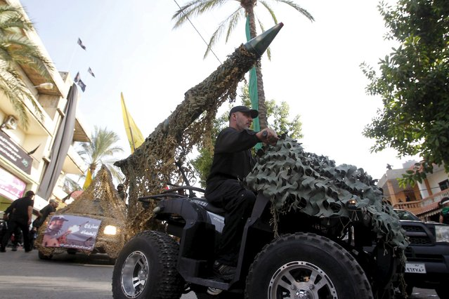A Hezbollah member drives a 4-wheel motorbike mounted with a mock rocket during a re-enactment of the battle of Kerbala during a mourning process, ahead of the day of Ashura, in Saksakieh village, southern Lebanon, October 18, 2015. (Photo by Ali Hashisho/Reuters)