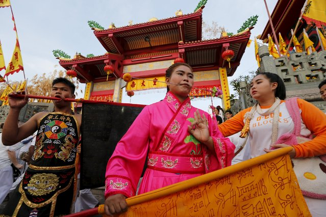 Devotees of the Chinese Jui Tui shrine walk with a piercing on their cheeks during a procession celebrating the annual vegetarian festival in Phuket, Thailand October 19, 2015. (Photo by Jorge Silva/Reuters)