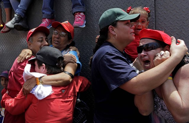 Supporters of Venezuela's late President Hugo Chavez embrace as the coffin containing his body passes in the street, March 6, 2013. (Photo by Rodrigo Abd/Associated Press)