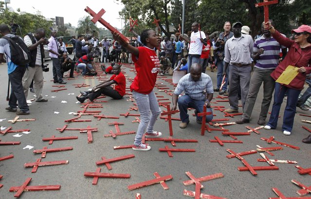 Protesters lay wooden crosses on the ground, symbolising people killed in a series of attacks, during the #OccupyHarambeeAve demonstration in Kenya's capital Nairobi November 25, 2014. (Photo by Thomas Mukoya/Reuters)