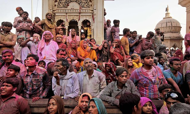 Hindu devotees wait outside the Ladali or Radha temple during the Lathmar Holi festival in Barsana. (Photo by Manish Swarup/Associated Press)