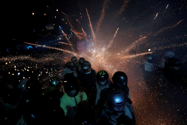 "Participators wearing motorcycle helmets get sprayed with firecrackers, during the ""Beehive Firecrackers"" festival at the Yanshui district in Tainan, Taiwan on March 1, 2018. (Photo by Tyrone Siu/Reuters)"
