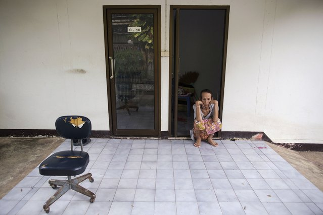 Somjit, a former dancer in a transgender club and an AIDS patient, passes the time in front of her accommodation at the Buddhist temple Wat Prabat Nampu where she has been living for seven years in Lopburi province, north of Bangkok November 30, 2014. (Photo by Damir Sagolj/Reuters)