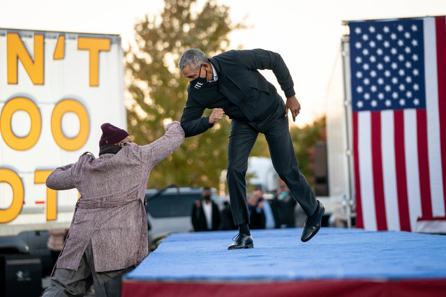 Former President Barack Obama bumps elbows with Tarence Wheeler, CEO of the Tarence Wheeler Foundation, as he arrives to speak during a drive-in campaign rally with Democratic presidential nominee Joe Biden at Belle Isle on October 31, 2020 in Detroit, Michigan. Biden is campaigning with Obama on Saturday in Michigan, a battleground state that President Donald Trump narrowly won in 2016. (Photo by Drew Angerer/Getty Images)
