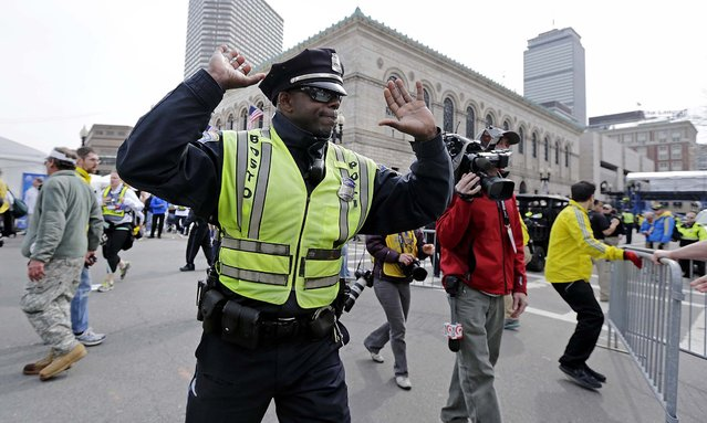 A Boston police officer clears Boylston Street following the explosions. (Photo by Charles Krupa/Associated Press)