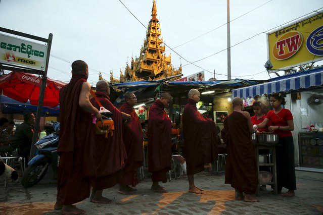 Buddhist monks line up to receive donated rice outside Mahamuni temple in Mandalay October 6, 2015. Buddhist-majority Myanmar goes to the polls on November 8 in an election billed as Myanmar's first free and fair ballot in 25 years. (Photo by Jorge Silva/Reuters)