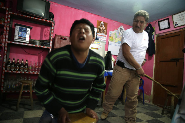 "In this June 7, 2014 file photo, 17-year-old Miguel Chusqui grimaces in pain as he is lashed by a ""rondero"", a member of a citizen vigilante group known as a ""ronda urbana"", or urban patrol, in Cajamarca, Peru. Chusqui was sentenced to five lashes for stealing a laptop. Rondas only handle cases that authorities consider minor, settling property and debt disputes, family quarrels and marital infidelities. (Photo by Martin Mejia/AP Photo)"