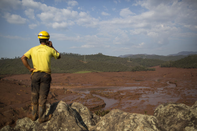 A rescue worker observes the destruction at the small town of Bento Rodrigues after a dam burst on Thursday, in Minas Gerais state, Brazil, Friday, November 6, 2015. (Photo by Felipe Dana/AP Photo)
