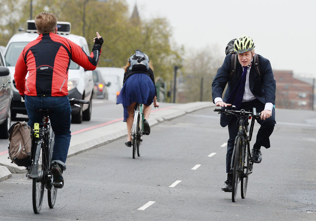 A commuter gestures to Boris Johnson as he rides across Vauxhall Bridge in London, England on November 19, 2015. The London mayor was opening a cycle superhighway. (Photo by John Stillwell/PA Wire)
