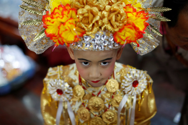 August, 8, is dressed up for an annual Poy Sang Long procession, part of the traditional rite of passage for boys to be initiated as Buddhist novices, in Mae Hong Son, Thailand, April 3, 2018. (Photo by Jorge Silva/Reuters)