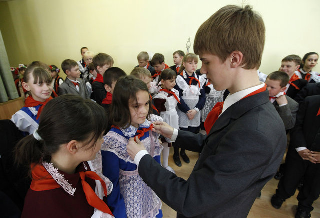 A pioneer ties red neckerchiefs, a symbol of the Young Pioneer Organisation, during a ceremony for the inauguration of 55 newly adopted members on the day of its anniversary at school-lyceum number 12 in Russia's Siberian city of Krasnoyarsk May 19, 2011. (Photo by Ilya Naymushin/Reuters)