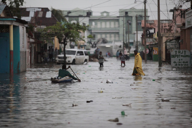 People walk in a flooded street during rain after Hurricane Matthew in Les Cayes, Haiti, October 21, 2016. (Photo by Andres Martinez Casares/Reuters)