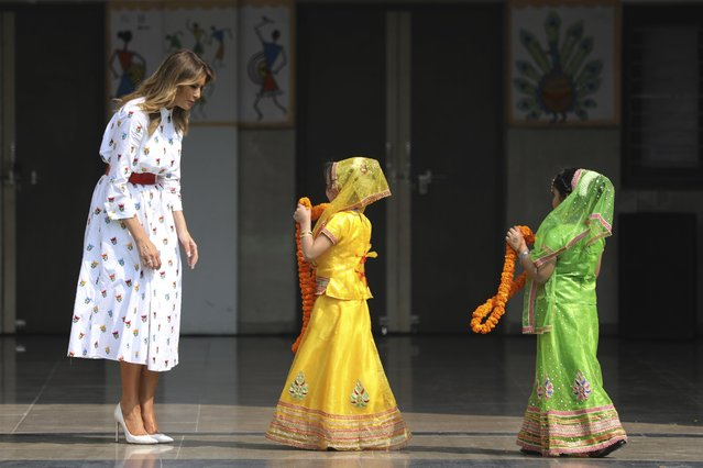 U.S. first lady Melania Trump waits to be garlanded by two children at Sarvodaya Co-Educational Senior Secondary School in New Delhi, India, Tuesday, February 25, 2020. (Photo by Altaf Qadri/AP Photo)