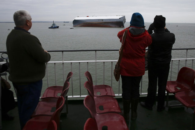 Passengers aboard a car ferry look out towards the hull of the Hoegh Osaka ro-ro cargo ship, operated by Hoegh Autoliners AS, as it sits grounded on Bramble Bank in the Solent near Cowes, on the Isle of Wight, U.K., on Monday, January 5, 2015. The car transporter was deliberately grounded after developing a list, shortly after it left the Port of Southampton. (Photo by Simon Dawson/Bloomberg)
