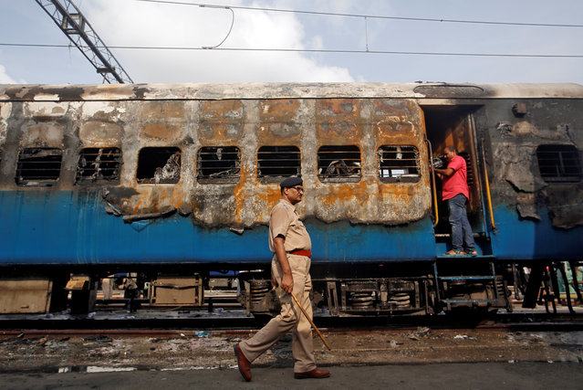 A police officer walks past a damaged coach of a passenger train after it caught fire at a railway station in Mumbai, India, May 29, 2018. (Photo by Francis Mascarenhas/Reuters)