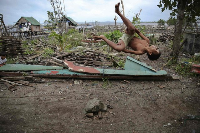 A boy does a flip in the coastal part of Tacloban, that was destroyed by Typhoon Haiyan, January 16, 2015. (Photo by Damir Sagolj/Reuters)