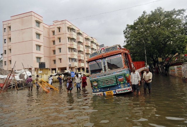 People wade near a stranded truck in a flooded locality in Chennai, India, December 5, 2015. (Photo by Anindito Mukherjee/Reuters)