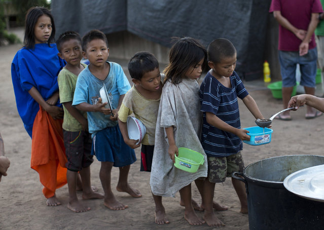 In this November 19, 2015 photo, students with receptacles line up for a serving of banana porridge provided by a government food program targeting public schools, in Pichiquia, an Ashaninka community in Peru's Junin region. An organization of Ashaninka representatives, known by its Spanish initials as CARE, says some 80 percent of children under age 5 suffer chronic malnutrition. (Photo by Rodrigo Abd/AP Photo)