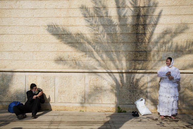 A Christian Orthodox pilgrim get dry in the sun after a bathe in the Jordan river during a baptism ceremony at Qasr-el Yahud near the West Bank town of Jericho, Sunday, January 18, 2015. (Photo by Oded Balilty/AP Photo)