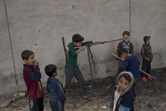 Children play in Qayara, some 50 kilometers south of Mosul, Iraq, Thursday, November 10, 2016. (Photo by Marko Drobnjakovic/AP Photo)