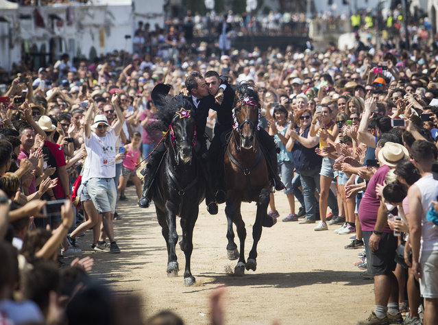 """Two riders kiss while galloping during the traditional San Juan (Saint John) festival in the town of Ciutadella, on the Balearic Island of Menorca on June 24, 2018, on the eve of Saint John's Day. During the island's San Juan Festival, held each year on June 23 and 24, Minorcan racehorses gallop and prance on their hind legs through the streets of Ciutadella in honour of the town's patron saint. As the """"caixers"""" (horse riders) ride together in a parade, spectators attempt to pat the horses' chests to get good luck. (Photo by Jaime Reina/AFP Photo)"""