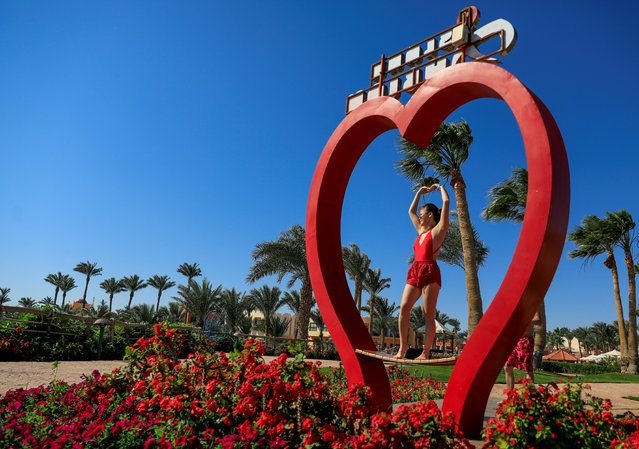 A tourist poses for a photo with a heart-shaped decoration on Valentine's Day at Nubian Village hotel in the Red Sea resort of Sharm el-Sheikh, Egypt on February 14, 2021. (Photo by Amr Abdallah Dalsh/Reuters)