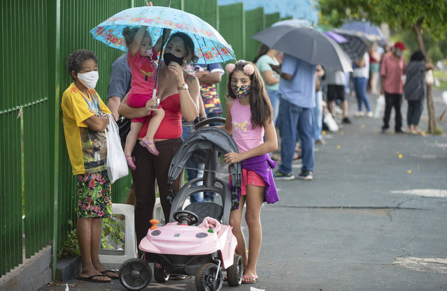 People wait in line outside a public school to get a shot of China's Sinovac CoronaVac vaccine in Serrana, Sao Paulo state, Brazil, Wednesday, February 17, 2021. Brazil's Butantan Institute has started a mass vaccination on Wednesday of the city's entire adult population, about 30,000 people, to test the virus' behavior in response to the vaccine. (Photo by Andre Penner/AP Photo)