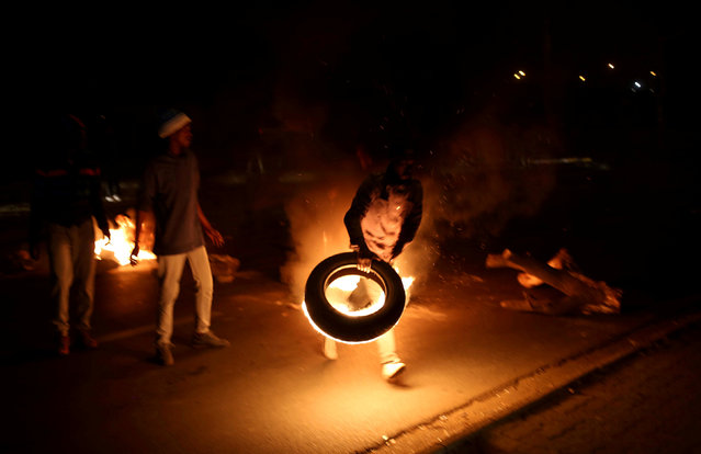 A man blocks a road with a burning tyre while protesting against electricity cuts in Klipspruit Soweto, Johannesburg, South Africa, July 4,2018. (Photo by Siphiwe Sibeko/Reuters)