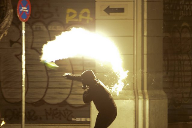 A hooded protester throws a petrol bomb to riot policemen during clashes, following a rally marking the 43rd anniversary of a 1973 student uprising against the military dictatorship that was ruling Greece, in Athens, Greece, November 17, 2016. (Photo by Yannis Behrakis/Reuters)