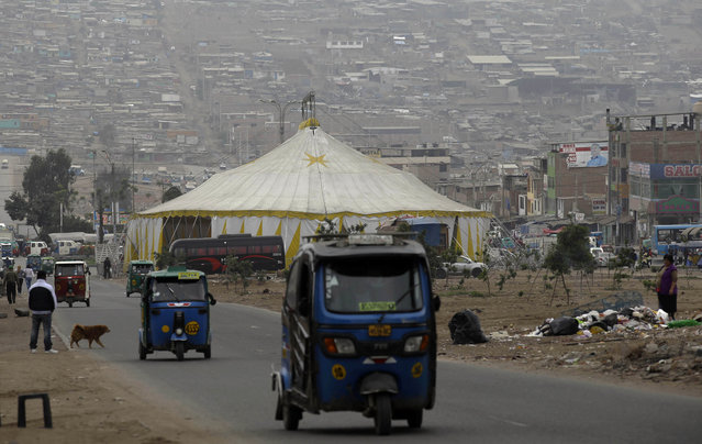 In this July 13, 2018 photo, taxi drivers pass La Panfila Circus tent set up in the shantytown of Villa El Salvador in Lima, Peru. Family circuses maintain much of the old-time traditions of the past: Clowns perform in makeup under tents with a traditional cone-shaped roof and a simple dirt stage. (Photo by Martin Mejia/AP Photo)
