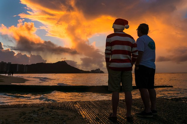 Tourists watch the Christmas Day sunrise behind Diamond Head from Waikiki Beach in Honolulu, Friday, December 25, 2015. (Photo by J. David Ake/AP Photo)