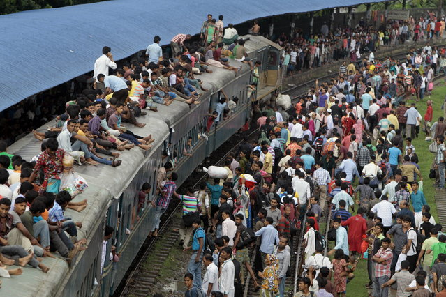 Bangladeshi passengers sit on the roof of an overcrowded train as others wait on the platform as they try to reach their homes to celebrate Eid al-Fitr in Dhaka, Bangladesh, Wednesday, August 7, 2013. Muslims across the world are preparing for the arrival of Eid al-Fitr, the festival marking the end of the Muslim fasting month of Ramadan. (Photo by A.M. Ahad/AP Photo)