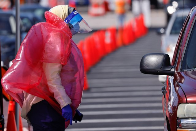 A worker's protective gear is blown by strong winds at a large vaccination site during the outbreak of the coronavirus disease (COVID-19) in Inglewood, California, U.S., March 15, 2021. (Photo by Mike Blake/Reuters)