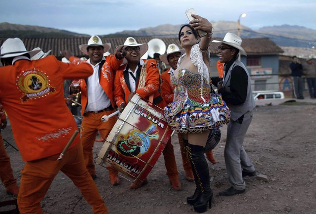"""In this Sunday, August 5, 2018 photo, transgender Carolina, dressed as a """"china"""", poses for a photo with Majestic Union band members during celebrations honoring Our Lady of Copacabana, in Cuzco, Peru. Despite the persistent discrimination suffered by members of the LGBT community in the country, Carolina says she and her friends are invited every year to take part in the religious celebration. """"I never feel discrimination"""", said Carolina, """"and sometimes I receive a little money for my dancing"""". (Photo by Martin Mejia/AP Photo)"""
