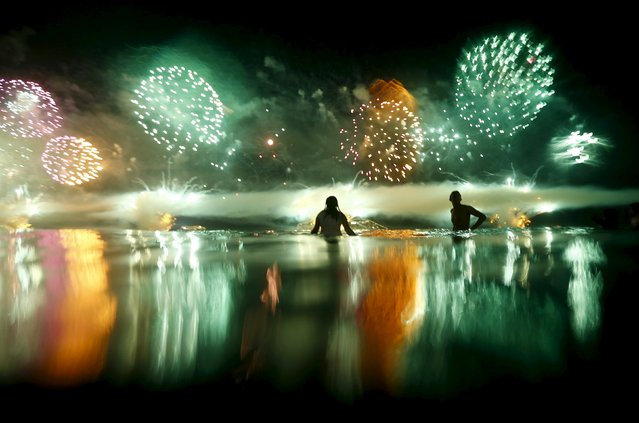 People watch as fireworks explode over Copacabana beach during New Year celebrations in Rio de Janeiro, Brazil, January 1, 2016. (Photo by Ricardo Moraes/Reuters)