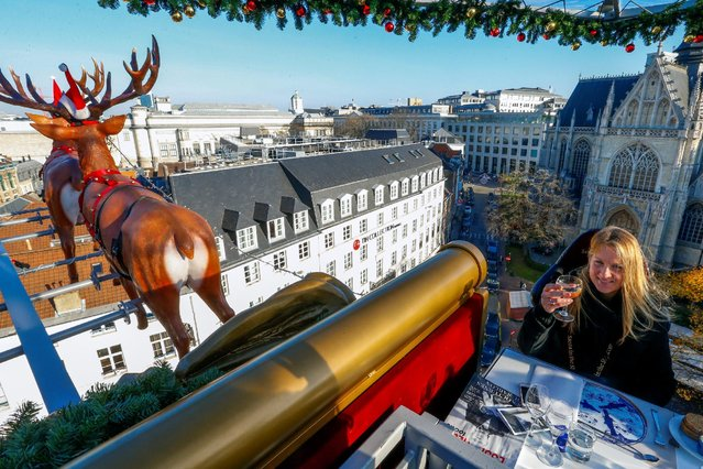 "A guest enjoys dinner at the table ""Santa in the sky"", lifted by a crane and decorated to match the appearance of a ""Santa Sleigh"" as part as the Christmas festivities, in Brussels, Belgium, November 25, 2016. (Photo by Yves Herman/Reuters)"
