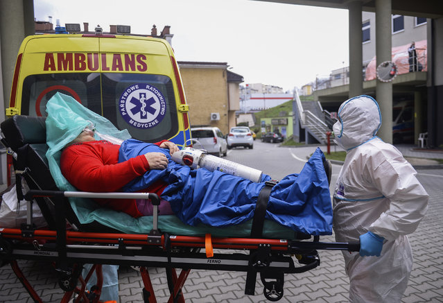 Paramedics arrive with a patient suffering from COVID-19 at the hospital in Bochnia, Poland, Sunday, April 4, 2021. Polish hospitals struggled over the Easter weekend with a massive number of people infected with COVID-19 following a huge surge in infections across Central and Eastern Europe in recent weeks. Tougher new pandemic restrictions were ordered in Poland for a two-week period surrounding Easter in order to slow down the infection rate. (Photo by Omar Marques/AP Photo)