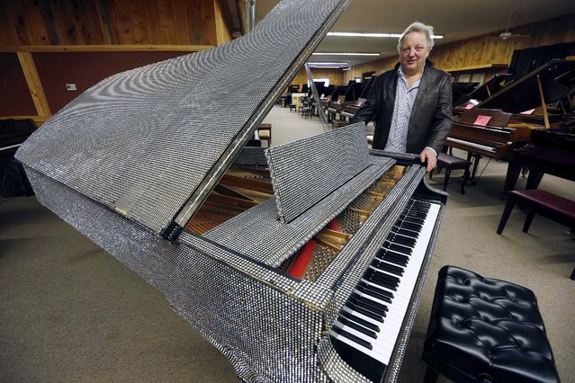 In this Saturday, January 24, 2015 photo, Rob Norris, owner of the Piano Mill in Rockland, Mass., stands beside a piano once owned by Liberace. A section of roof collapsed into the music store's showroom under the weight of snow Tuesday, February 10, 2015, after Rockland received 29 inches of new snow the previous day. (Photo by Michael Dwyer/AP Photo)