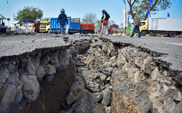 People walk on a road damaged by yesterday's large earthquake at Kayangan Port in Lombok, Indonesia August 20, 2018 in this photo taken by Antara Foto. (Photo by Ahmad Subaidi/Reuters/Antara Foto)