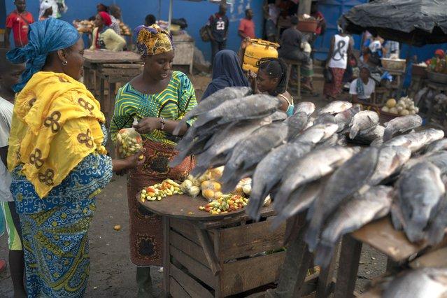 A woman sells her goods at a local market in Abobo neighborhood, suburbs of Abidjan, Ivory Coast, Sunday, November 1, 2020. (Photo by Leo Correa/AP Photo)