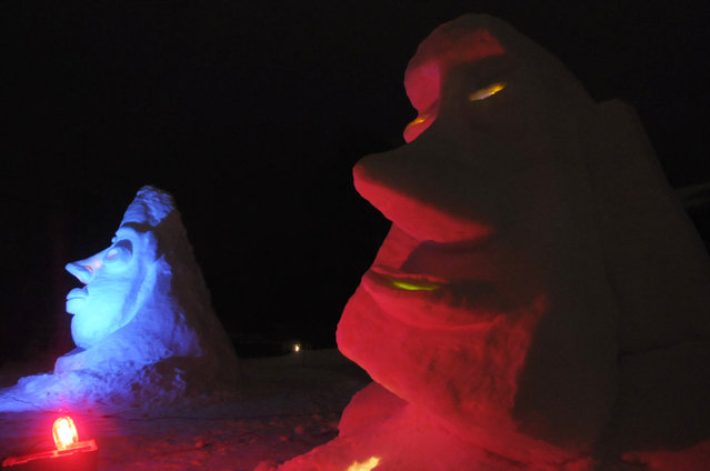 In this photo taken Wednesday, February 11, 2015, a pair of snow sculptures, inspired by African masks and Easter Island, are illuminated outside Mark Lee's home in Ann Arbor, Mich. (Photo by Nicole Hester/AP Photo/The Ann Arbor News)