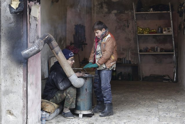 Boys warm themselves around a heater inside a shop during cold weather in the rebel-controlled area of Maaret al-Numan town in Idlib province, Syria, January 4, 2016. (Photo by Khalil Ashawi/Reuters)