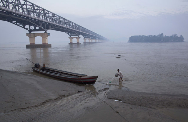 A boatman collects a bucket of water from the Thanlwin River in a misty morning in Mawlamyine, eastern Mon state, Myanmar Thursday, February 12, 2015. (Photo by Gemunu Amarasinghe/AP Photo)