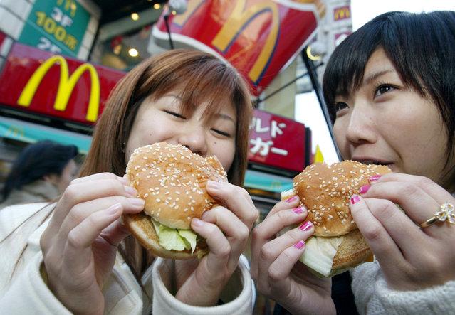 Japanese teenagers enjoy McDonald's Big Macs in Tokyo December 24, 2003. (Photo by Eriko Sugita/Reuters)