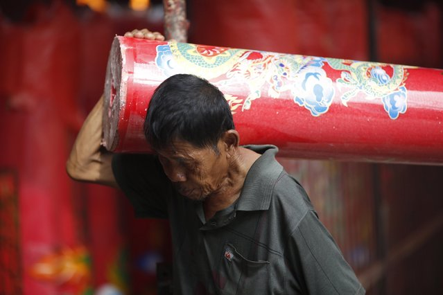 A worker carries a large candle at Petak Sembilan Chinese Buddhist temple on the eve of Chinese Lunar New Year celebrations in Jakarta, February 18, 2015. (Photo by Darren Whiteside/Reuters)